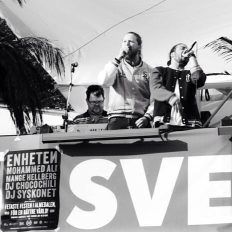 Bild på bandet Enheten som står bakom ett mixerbord och sjunger. Det är tre personer på bilden och de håller minkar i händerna. Bilden är svartvit