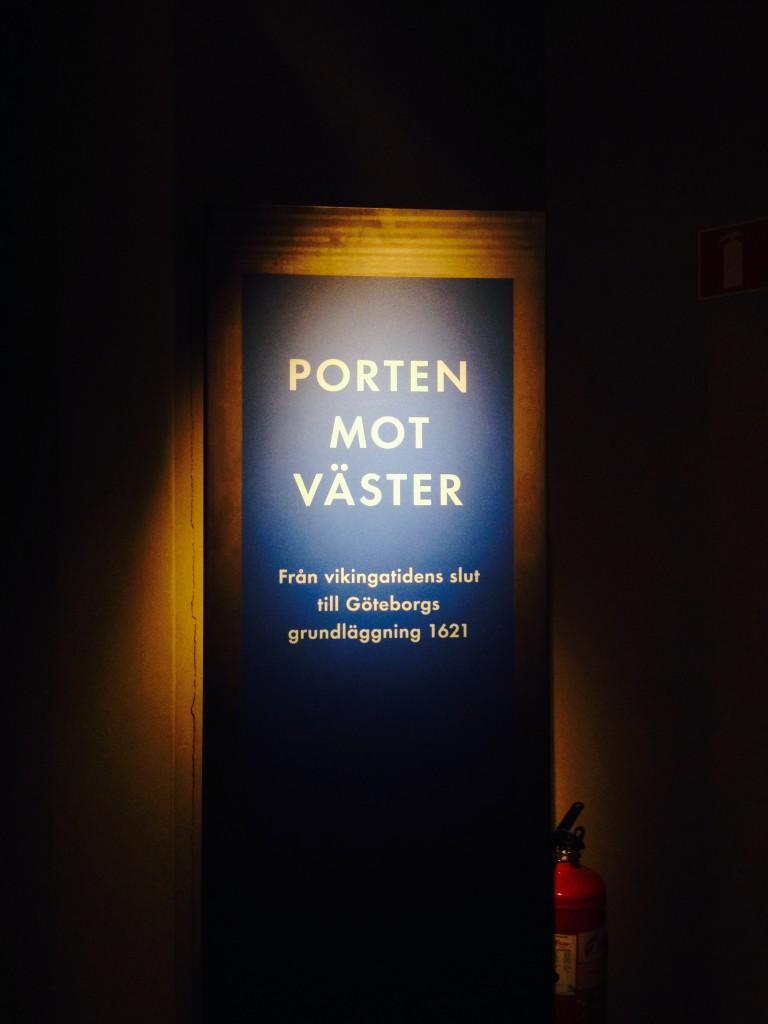 bild på en blå skylt där det står porten mot väster. Skylten är mörk och belyst med svagt ljus