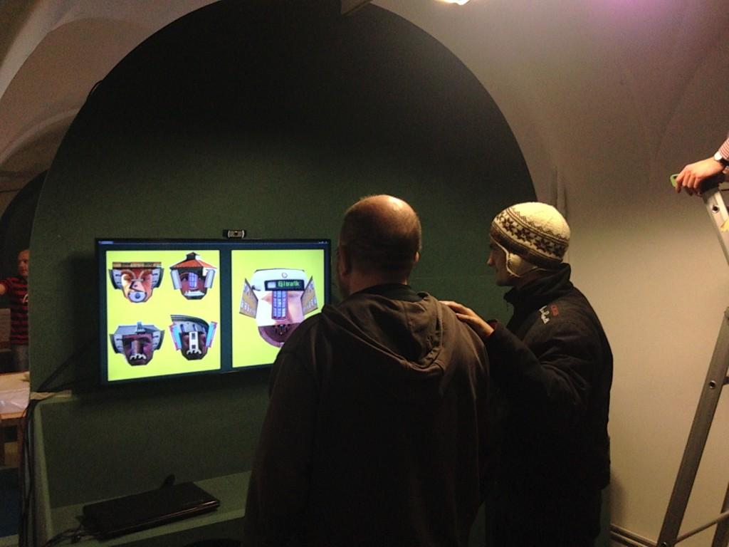 På bilden ser man två personer som tittar på två gula bildskärmar med figurer på. De står framför en grön vägg till vänster och en vit vägg till höger.