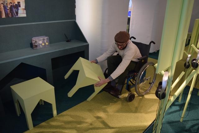 Bilden visar en person som sitte i en rullstol och försöker flytta på en pall. Pallen är tung och personen har svårt att flytta på den för att komma fram.