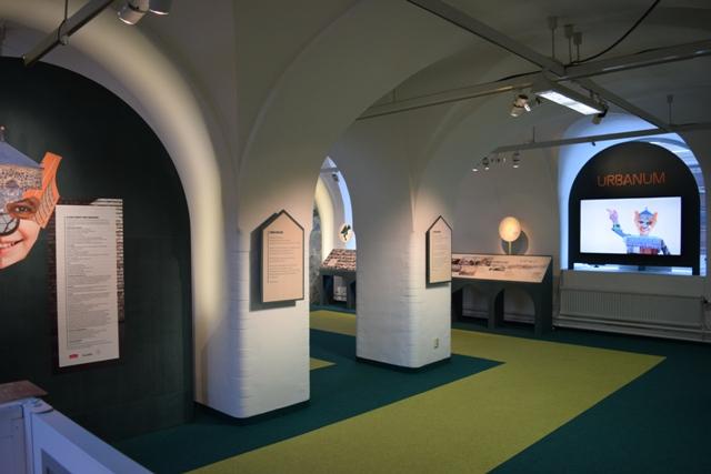 Bilden visar entren till utställningen Urbanum. Det är två vita pelare med en utställningstext på. Golvet är klätt med en matta som är mörkgrön och ljusgrön.