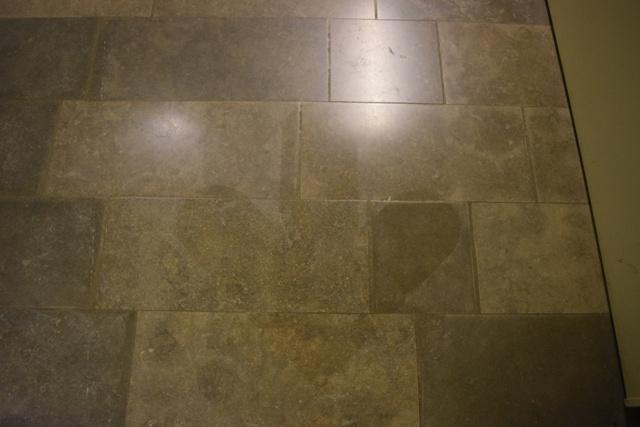 """Bilden visar spår efter en borttagen pil i golvet. Tidigare pekade pilen endast mot trappan och gav känslan av att detta var den """"rätta"""" vägen till utställningen. Nu är är istället hissen ich mattan likvärdiga ingångar till utställningen. Detta är viktigt för att alla ska känna sig välkomna."""