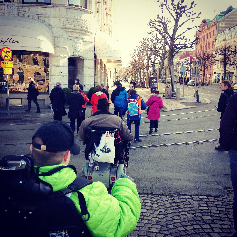 På bilden ser man flera testpiloter som går och kör permobil på en gata, över spårvagnsspår, det finns butiker och träd i bilden. Test av stadsrummet. Vilka platser är tillgängliga i Göteborgs innerstad?