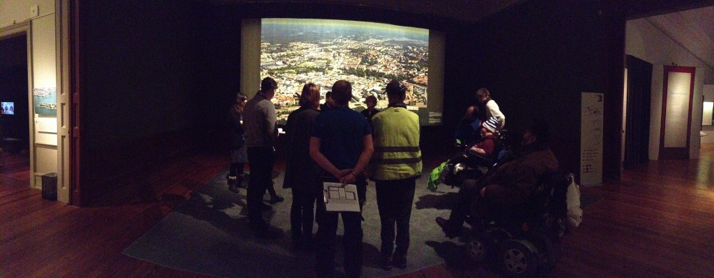 Vy över entréhallen, ett av uställningsrummen. I bakgrunden syns en stor bild av en karta över Göteborg. Framför den med ryggarna mot kameran står 6 workshopdeltagare. De står vända mot en person som talar.