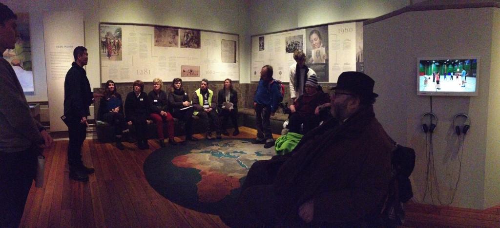 Bild från ett av utställningsrummen. Mot en bakre vägg på en bänk sitter fem workshopdeltagare. Till höger om dem står två personer och längst till vänster i bild är en person som sitter i en permobil. I mitten av bilden finns en rund matta med ett motiv av en karta.