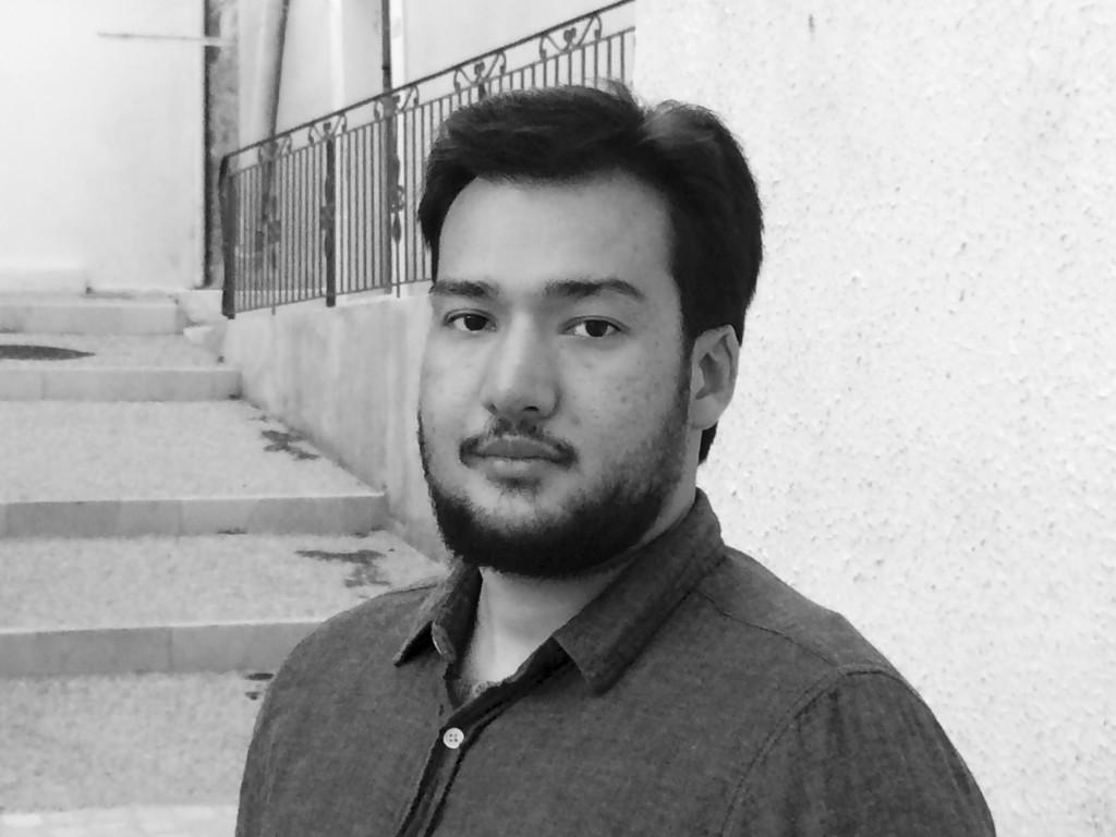 På den svartvita bilden har han mörkt hår, skägg och en mörk skjorta med vita knappar. Han står framför en vägg, trappa och ett staket ovanför trappan.