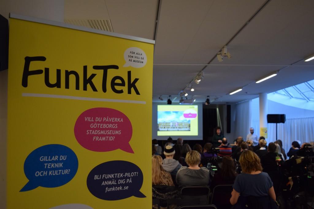 Bilden visar en gul vepa, till vänster om bilden där det står Funktek. Till höger om bilden sitter det människor på stolar med ansiktena vända mot en scen så vi bara ser ryggen på publiken.