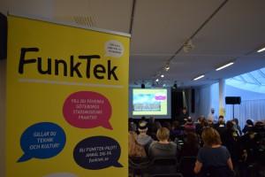 Bilden visar en gul vepa till vänster om bilden där det står Funktek. Till höger om bilden sitter det människor på stolar med ansiktena vända mot en scen så vi bara ser ryggen på publiken.