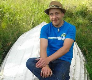 På bilden ser man Fredrik sittande på en upp- och nedvänd vit båt som ligger i högt gräs. Han har en blå t-shirt, blå jeans, brun hatt, halsband, armband och ringar.