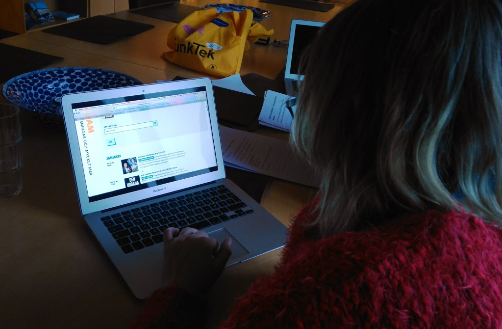 Bilden visar Frida som sitter framför en dator och utvärderar tillgängligheten på Göteborgs Stadsmuseums hemsida. Frida är vänd bort mot kameran och en kan se Fridas rygg och hennes lurviga röda tröja. Frida har blont hår till axlarna och svarta glasögon. Hon har datorn framför sig på ett stort bord i ljust trä. Framför datorn står en skål och en gul tygpåse som det står funktek på.