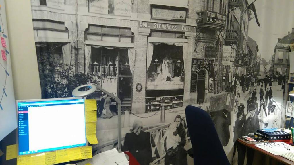 Arbetsvrån: En stor bild på ett gammalt Göteborg och en dator där det hänger flera post-it-lappar.
