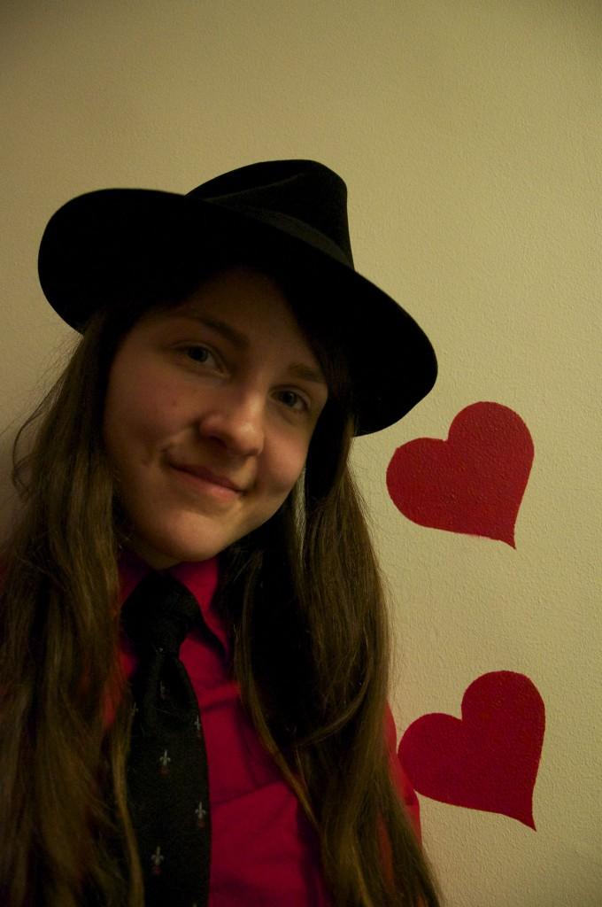 På bilden ser man Angela. Hon har en svart hatt, svart slips med prickar, en röd skjorta och brunt hår. På den vita väggen bakom henne, är det målat två röda hjärtan.