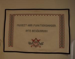 På bilden ser man en tavla med texten: museet har funktionshinder, inte besökarna!
