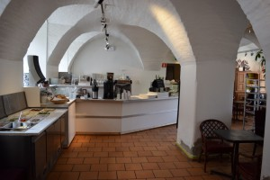 På bilden ser man restaurangen. Det är tegelgolv med vita valv och en disk med kaffekanna och olika matvaror på.