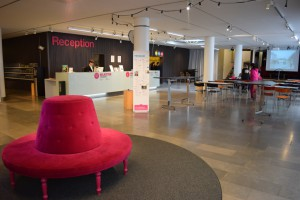 På bilden ser man receptionen. Framför den står en rosa, rund soffa, rummet är kanske 30 meter långt och 20 meter brett. Längst bort till höger ser man en filmduk och stolar och bord.