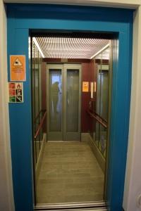 Hissen till olika utställningar. Den har en blå öppning och är kanske 4 meter lång och 1,5 meter bred.
