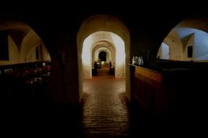 Ett mörkt rum med flera valv, tegelgolv med lösa stenar. Det är säkert 40 meter långt och 20 meter brett.