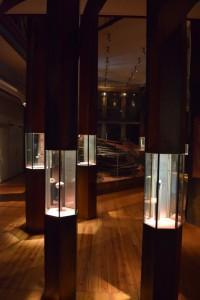 På bilden ser man upplysta montrar på ett trägolv. Det är dunkelt i utställningen.
