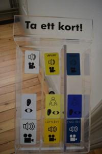 På bilden ser man vita, gula och blå kort som används för att lyssna på utställningen Omänskligt.