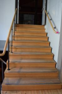 På bilden ser man en trappa med handtag. På högra sidan slutar handtaget tvärt och man riskerar att ramla.