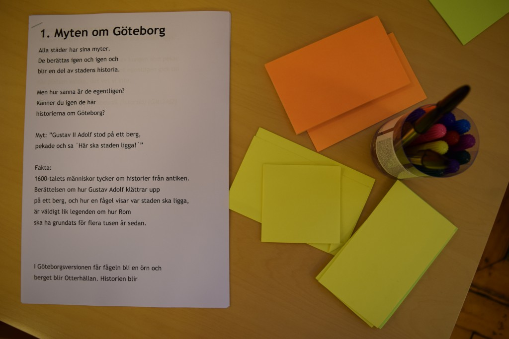 """Bilden visar ett bord i ljust trä. Till vänster på bordet ligger ett papper med en text som har rubriken """"Myten om Göteborg"""". Till vänster på bordet ligger det pennaor och oskrivna post-it-lappar."""