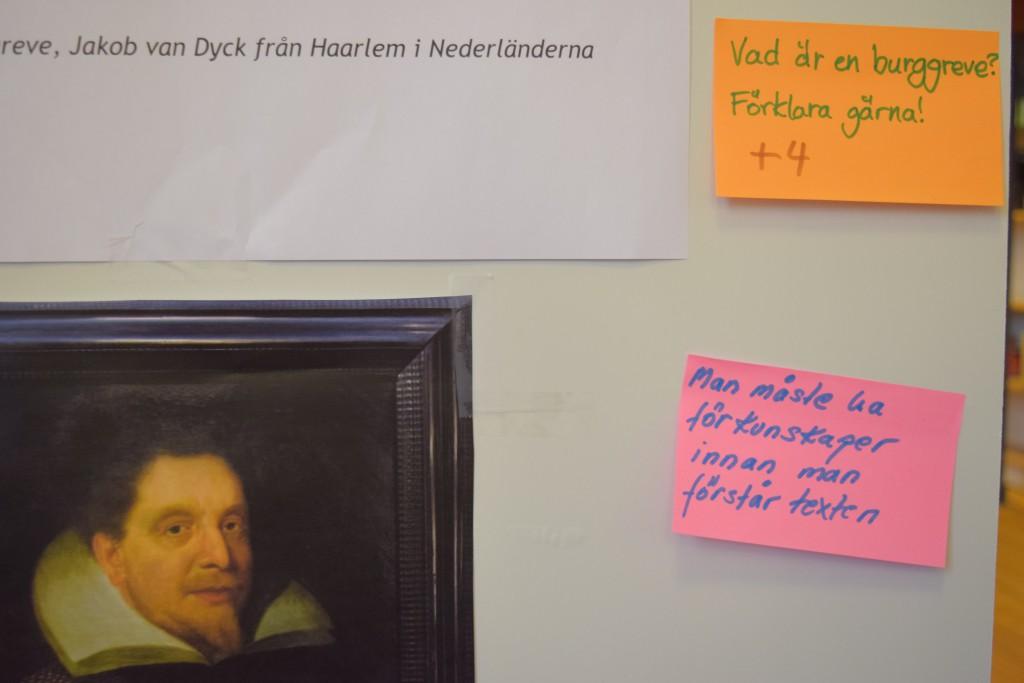 """Bilden visar en anslagstavla. Till vänster på anslagstavlan hänger en bild på en person med mustash och skägg på hakan. Personen bär 1600-tals-kläder. Till höger sitter två post-it-lappar. På den ena står det: """"Vad är en burgreve? Förklara gärna!"""". På den andra står det: """"Man måste ha förkunskaper innan men förstår texten""""."""