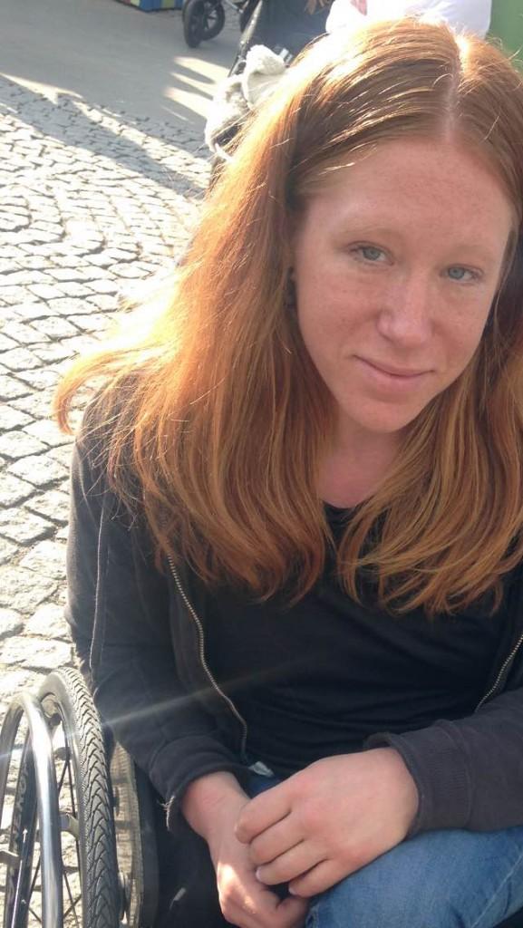 På bilden ser man Felicia. Hon har rött långt hår, svart tröja med grå huvtröja. Hon sitter i en rullstol på kullerstenar.