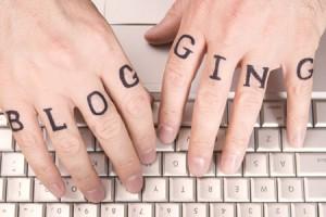 """På bilden ser man två händer på ett tangentbord och texten """"blogging"""" på dem."""