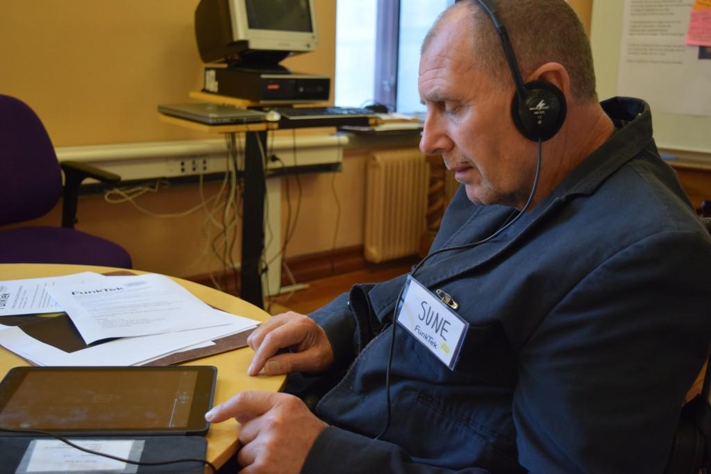 """Bilden visar en person som sitter vid ett bord. Personen lyssnar på inspelade texter med hjälp av en iPad och hörlurar. Personen har kort snaggat hår och har en namnlapp på sig där det står skrivet: """"Sune""""."""