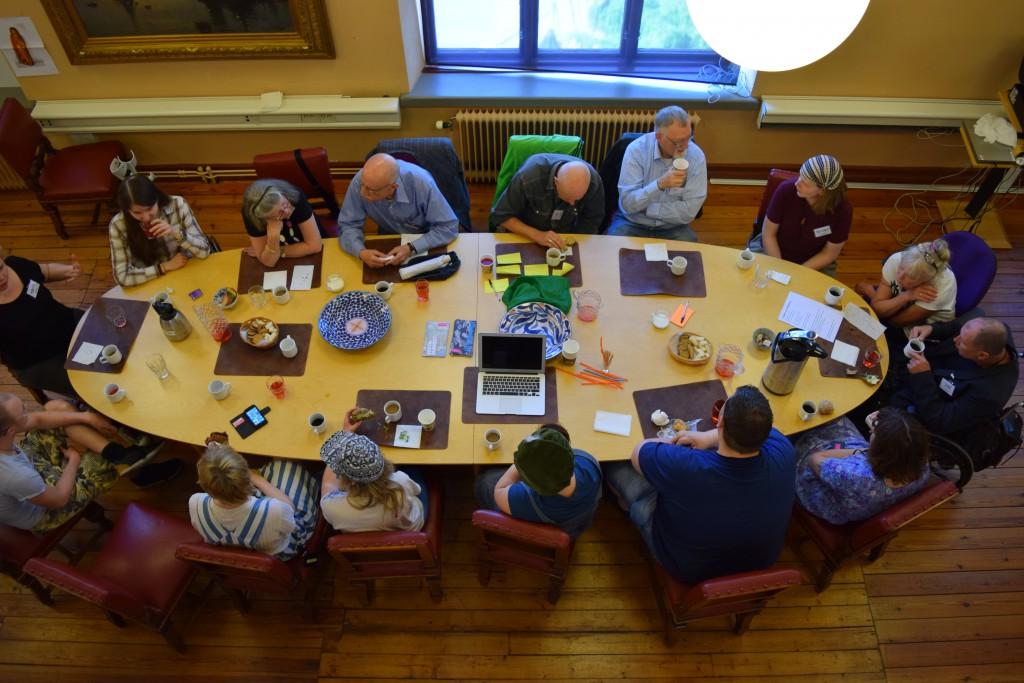 Bilden visar ett stort bord ovanifrån. Bordet är ovalt och kring bordet sitter 15 personer och fikar och pratar.