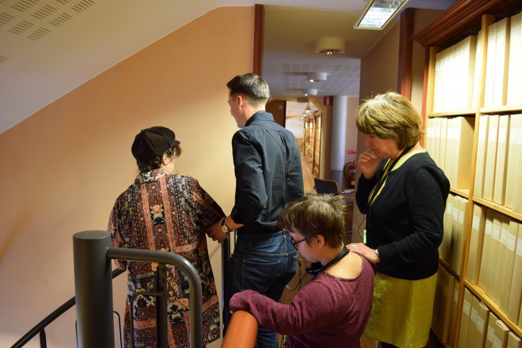 På bilden syns fyra personer som ledsagar varandra. De ska just bege sig ner för en trappa. till höger om dem syns bruna mappar. Till vänster syns en vägg som persikofärgad. trappans räcke anas. Räcket är mörkt grått.