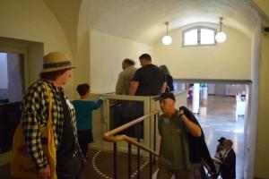 En del av gruppen på väg till biblioteket, där workshopen ägde rum. På bilden ser man åtta personer, några åker i en hiss, några går i en trappa.