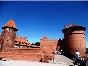 På bilden ser man det vackra slottet Malbork: det syns tre torn och flera murar i röd tegel. Jag gillar slottet väldigt mycket, men det är svårt att besöka om du sitter i rullstol eller har en synnedsättning.