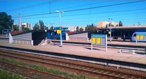 På bilden ser man en tågstation med ett tåg som står inne och två perronger. Det är som oftast var fallet, en tågstation utan hiss eller markering för de med synnedsättning.