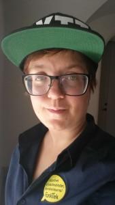 """Bilden föreställer Jenny som har glasögon och rött hår. På den marinblå skjortan nära kragen sitter det fast ett gult tygmärke, format som en pratbubbla. I pratbubblan står det: """"Kulturlivet har funktionshinder, inte människorna!"""" Och sedan står även Funkteks logga i lite större bokstäver på tygmärket. Jenny har även på sig en keps. Skärmens undersida på kepsen är grön. Tryckt på kepsen står det """"LYTT"""" i stora bokstäver. Jenny småler och står i snett motljus."""
