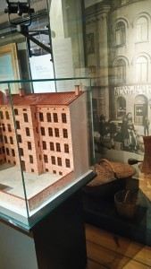 Bilden visar två montrar: en monter med en fabrik i tegel, står framför en text och monter med diverse föremål. Det är svårt att ta sig fram men även att hitta texten.