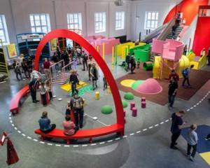 """Megamind på Tekniska museet. Det är en ca 30 gånger 30 meter stor sal som är fylld med diverse redskap för att testa fysiken och balansen. Mitten av rummet täcks av en några meter hög röd halvcirkel. Det finns röda, gröna och rosa """"kuddar"""" och ställningar att ta sig uppför och igenom. Till vänster står en roddmaskin och en slalommaskin där man ställer sig i och ser sig åka på en skärm. Gömt till höger finns en dansmaskin och möjlighet att gå på lina."""